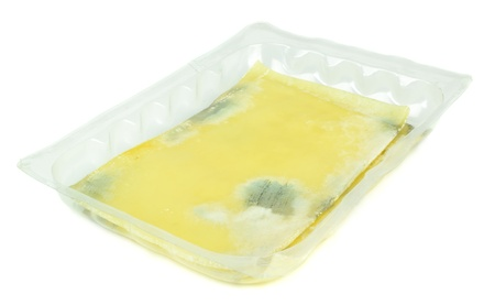 mouldy: Slices of rotten mouldy cheese on a white background