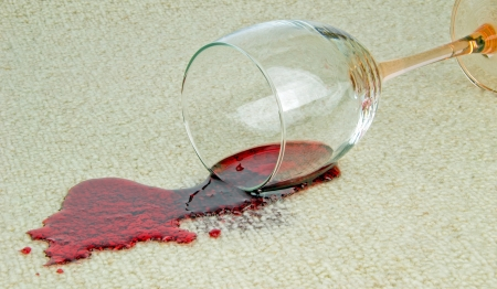 derrames: Un vaso de vino tinto derramado sobre una alfombra Foto de archivo
