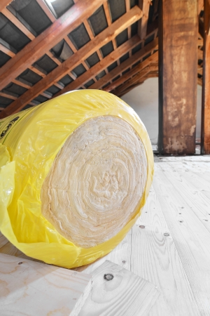 insulating: A roll of insulating glass wool on an attic floor Stock Photo