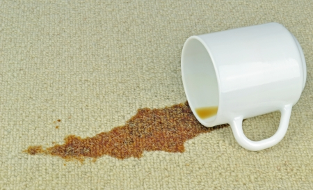 A spilled cup of coffee on a carpet with stain Stock Photo
