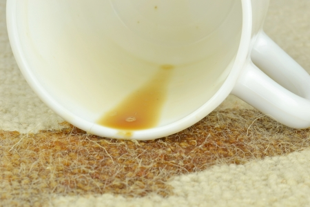 A close up of a spilled cup of coffee on a carpet  Stock Photo
