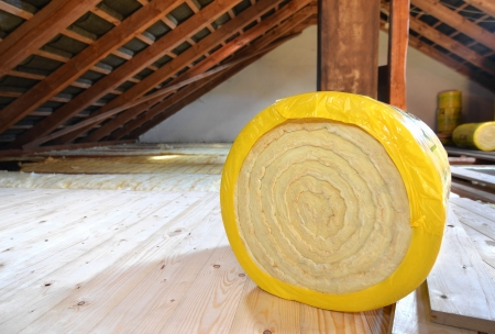 fiberglass: A roll of insulating glass wool on an attic floor Stock Photo