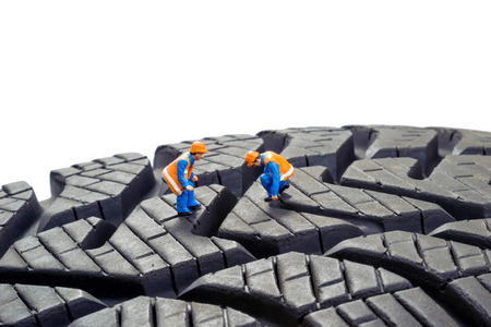 tyre tread: Miniature workers checking the depth tread on a car tyre