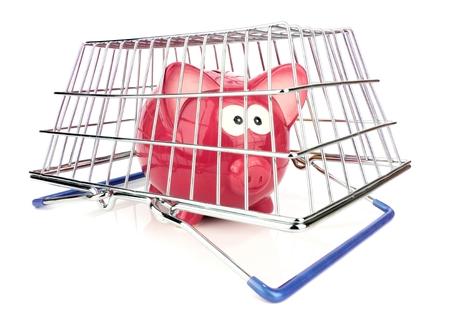 A piggy bank trapped under a shopping basket photo