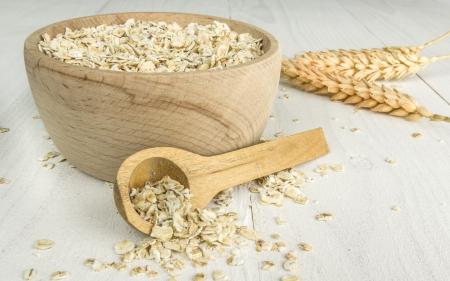 avena en hojuelas: Cuenco de madera y cuchara con copos de avena en la mesa de madera