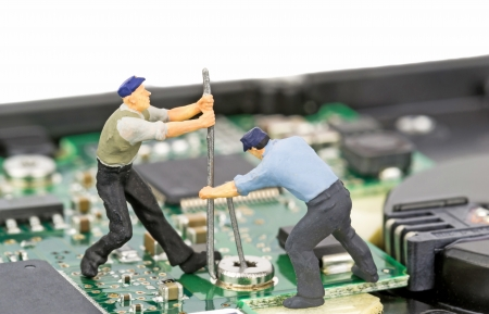 computer problems: Miniature engineers repairing a computer hard drive