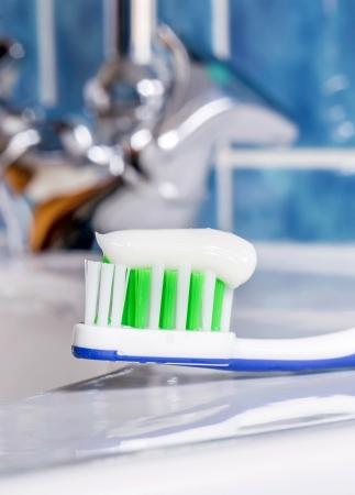 pasta dental: Un cepillo de dientes con un poco de pasta de dientes en el lavabo Foto de archivo