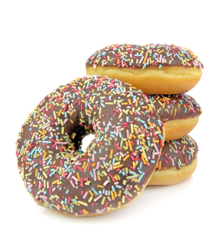 Chocolate doughnuts with coloured sprinkles on a white background photo