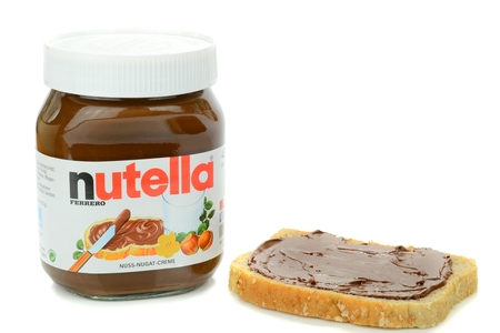 ferrero: NIEDERSACHSEN, GERMANY SEPTEMBER 13, 2014: A glass jar of Ferrero Nutella chocolate spread with slice of bread on a white background