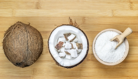 desiccated: Bowl of desiccated coconut whole and chunks on wooden table background