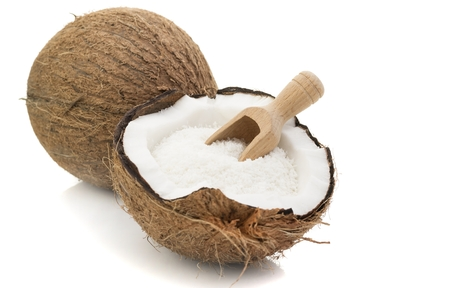 shredded coconut: A coconut with desiccated coconut and scoop on white background Stock Photo