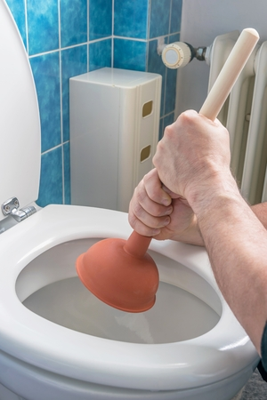 unblock: A plumber using a plunger to unblock a household toilet Stock Photo