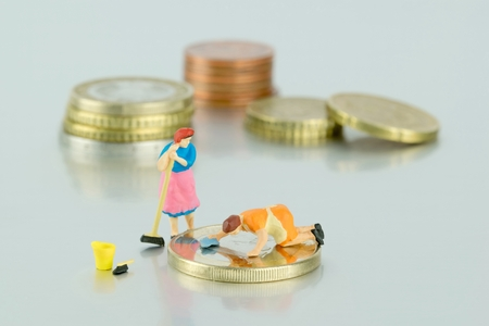 Minimumloon concept miniatuur dame schoonmaken van geld Stockfoto