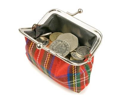 libra esterlina: Un bolso abierto lleno de dinero monedas brit�nicas sobre un fondo blanco