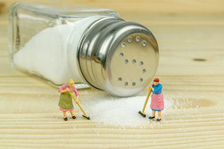 salt crystal: Miniature toy housewives figures cleaning up spilled salt on wooden table