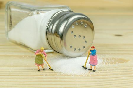 Miniatuur speelgoed huisvrouwen cijfers opruimen gemorst zout op houten tafel