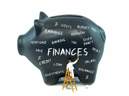outgoings: A selection of financial themed words on a piggy bank