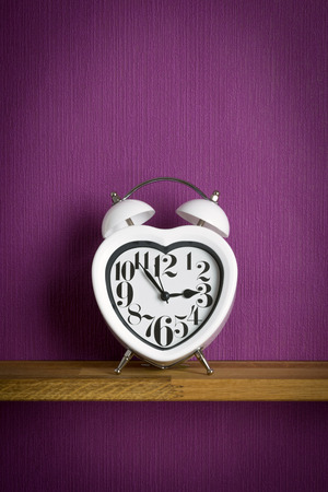 bell shaped: A heart shaped clock on a shelf with purple copy space background Stock Photo