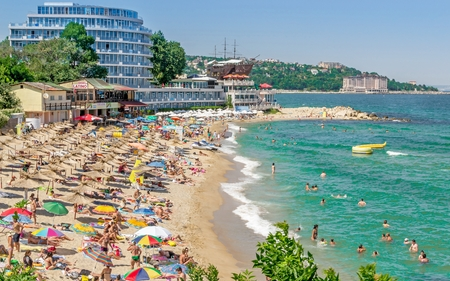 golden: GOLDEN SANDS, BULGARIA  - JULY 06, 2013: A crowded beach scene at the Golden Sands coastal resort in Bulgaria