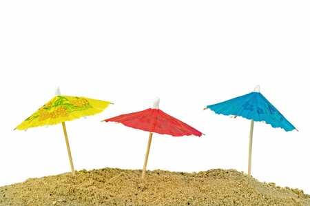 mini umbrella: Miniature paper sun umbrellas in sand with white background