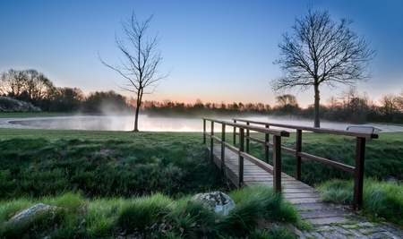 foot bridge: A wooden foot bridge at a misty lake during sunrise sunset Stock Photo
