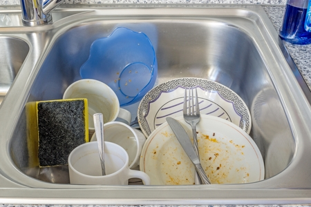 dirty: A small pile of dirty dishes in a kitchen sink
