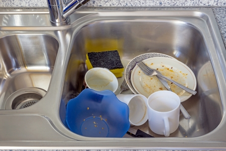 domestic chore: A small pile of dirty dishes in a kitchen sink