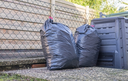 big bin: Plastic bin bags full of rubbish next to household bins