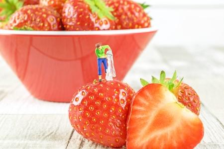 Conceito de higiene alimentar de uma figura em miniatura que limpa um morango. Imagens