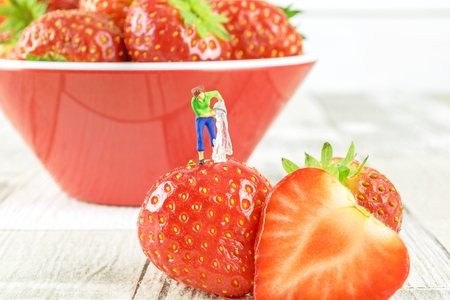 Food hygiene concept of a miniature figure cleaning a strawberry. Archivio Fotografico