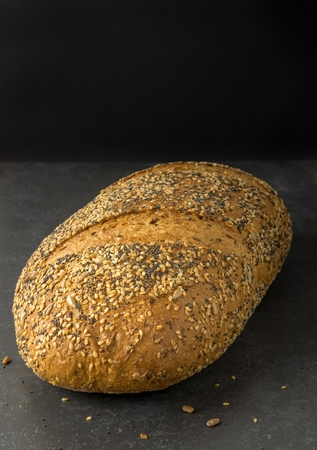 A loaf of wholemeal multi grain bread on dark background with copy space for your text