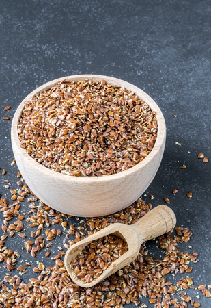 A wooden bowl and scoop with linseed on a granite stone background with copy space for your text.