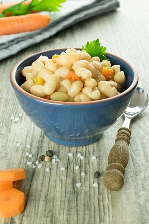A bowl of white beans and carrot stew on a rustic wooden table with utensils and ingredients