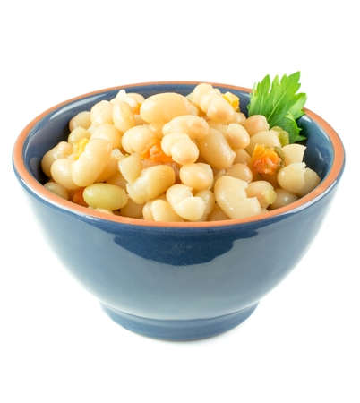 A bowl of white beans and carrot stew on a white background