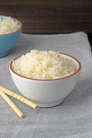 A bowl of cooked white rice on a linen towel with copy space for your text