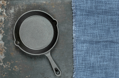 A flat lay image of an empty cast iron skillet and cloth on a used metal background with copy space for your text