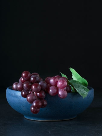 Red grapes in a blue bowl on a dark background with copy space for your text Banco de Imagens