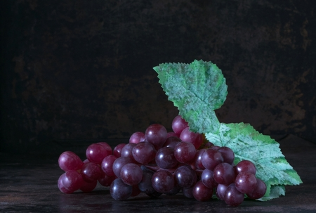 A bunch of red grapes on a rustic background with copy space for your text Banco de Imagens