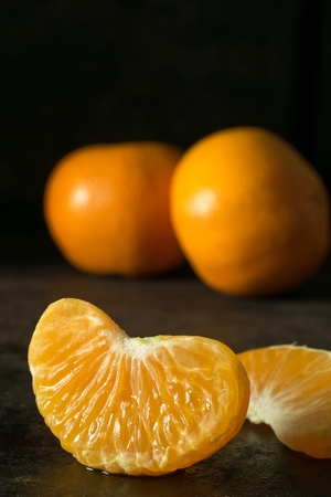 A close up of a juicy segment of an orange tangerine on a dark background with copy space for your text Banco de Imagens