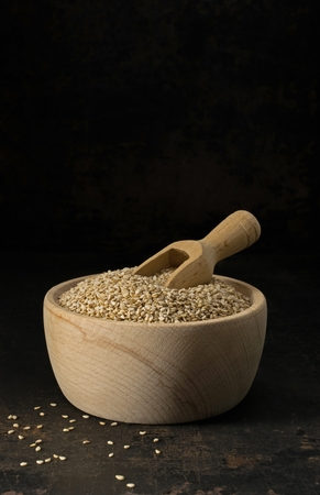 Sesame seeds in a wooden bowl with scoop on a low light background with copy space for your text Banco de Imagens