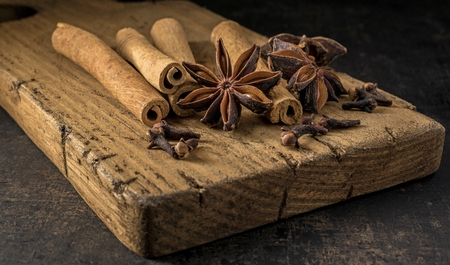 Aniseed star, cinnamon sticks and cloves ingredients for mulled wine on a rustic wooden chopping board.