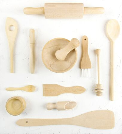 A flat lay overhead view of various wooden kitchen utensils on a white structured background