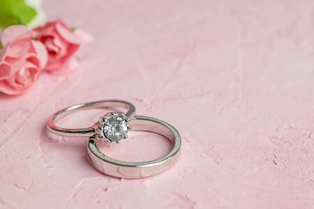 A pair of silver wedding rings on a pink textured surface with copy space for your text in the background.