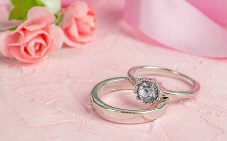 A pair of silver wedding rings on a pink textured surface with flowers and lace decorations in the background.