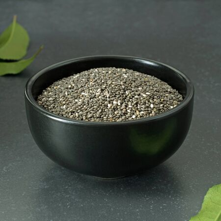 A serving of chia seeds in a black bowl on a dark stone surface with copy space for your text