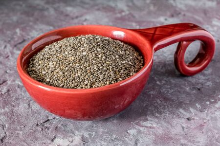 A serving of chia seeds in a red bowl on a stone granite surface