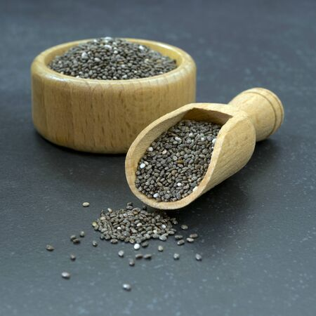 A close up of chia seeds in a wooden bowl and scoop on a dark stone surface