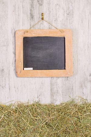 A wooden framed blackboard with chalk hanging on a rustic background with straw grass and copy space for your text or picture
