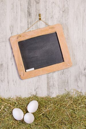 A wooden framed blackboard with chalk hanging on a rustic background with straw grass and fresh eggs. Copy space for your text or picture Banco de Imagens