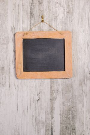 A wooden framed blackboard hanging straight on a rustic background with copy space for your text or picture